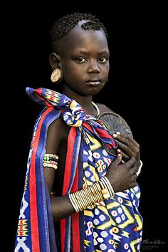 """Young Girl from the Mursi Tribe with a Lip Plate of her sister in her hands. The picture was taken in Omo Valley, South Ehiopia.  The Mursi or Mursu are living in Ethiopia's Omo Valley.  They are well known for their unique lip plates.  They are settled around the Omo River and in the Mago National Park.  Due to the climate, they move twice a year between the winter and summer months.  They herd cattle and grow crops along the banks of the Omo River.  The Series """"African Vogue"""" contains…"""