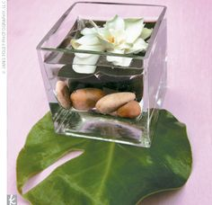 Other centerpieces included short square glass vases filled with river rocks and lotus flowers.