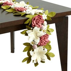 Featuring a spray of felted flowers, this stunning table runner is handmade by women in Kathmandu, Nepal.