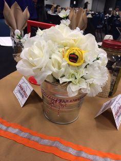 Fire department banquet - dollar store flower stems & floral foam, scraps of burlap, Sculpey clay helmets hot glued on the cutoff wire flower stems, baker's twine. #firemen #firefighter #banquet