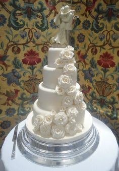 4 tier ivory wedding cake with cascading handmade sugar roses which were lightly dusted in a beautiful sparkling glitter (topper provided by bride and groom)