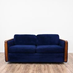 This Mid Century Modern loveseat is upholstered in a soft blue fabric. This vintage sofa has removable seat cushions, comfortable back cushions and wooden arms. Perfect for lounging! #midcenturymodern #sofas #loveseat #sandiegovintage #vintagefurniture