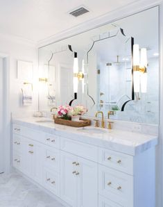 Bathroom Decor countertop Art deco mirrors are mounted to a frameless vanity mirror hung over a white dual washstand adorned with brass and glass pulls and a honed white marble countertop finished with brushed gold faucets. Decorative Bathroom Mirrors, Art Deco Bathroom, Art Deco Mirror, Bathroom Ideas, Elegant Bathroom Decor, Budget Bathroom, All White Bathroom, White Marble Bathrooms, Small Bathroom