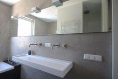 Badkamer voorzien van dubbele wastafel, ligbad, douche en toilet. Gedeeltelijk betegelt met grote tegels en pandomo stucwerk op de wanden. Ontwerp:Filiaal 4 i.s.m. Pieter de Boer