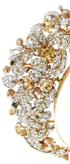 18 Karat Gold, Platinum and Diamond Tiara/Necklace, David Webb, designed as a meandering flowering vine, decorated with stylized acorns, set with numerous round diamonds signed Webb; with two detachable links measuring 1 inch each; also accompanied by three additional links, signed Webb; circa 1973; together with an 18 karat gold tiara fitting with maker's mark for Carvin French. Image Sotheby's. see nearby pin.