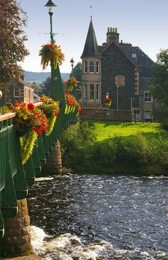 The River Earn flows underneath a flower decorated bridge in Comrie, Scotland.
