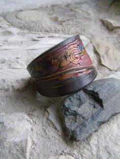 Kožený náramek šedočerný Náramek je vyrobený z kůže - hověziny, síla3,5 mma je zdobený / rytím / raznicemi vlisovaným vzorem / malováním / a dobarvený do šedočerné, vzor do pestrých barev. Délka vč. zapínání21,3 cm šířka uprostřed4,8cm. Zapínání je vyrobené z chirurgické ocele a patinované.
