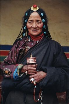 Tibetan elderly woman holding a prayer wheel.