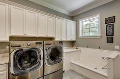 Gorgeous laundry room with an oversized pet washing station. Photo: Emerald Coast Real Estate Photography