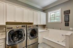 Gorgeous laundry room with an oversized pet washing station. Photo: Emerald Coast Real Estate Photography