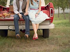 vintage farm styled engagement shoot, engaged couple holding hands in the back of an old truck bed