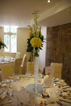 The tables were dressed with a combination of tall slim elegant vases topped with a hand tie of white Delphinium Elatum, yellow Eremurus, yellow Arum Lilies and yellow Roses and fabulous giant Martini Vase designs.