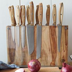 This would be really easy to make with a nice block of wood and a piece of Plexiglas! Just use screws with a few washers between the plexi and the wood to allow for the knives to fit in. I want this rustic-looking knife set from West Elm.