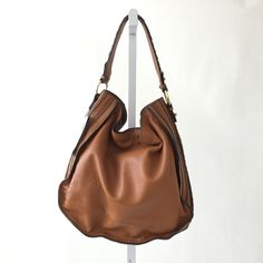 ZARA Cognac Leather Hobo Bag Warm brown genuine leather hobo style bag with braided detail on the side. Lines with inside pocket. Magnetic closure. Has original tags still attached. Note that leather may have imperfections due to nature of the material. Please carefully review each photo before purchase as they are the best descriptors of the item. My price is firm. No trades. First come, first served. Thank you! :) Zara Bags Hobos