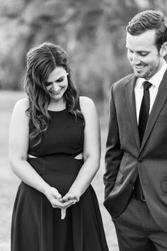 Couple looking at the bride's engagement ring in a high low black formal gown by Aidan Mattox and a suit and tie for San Diego engagement photos, Chic black and white modern and sophisticated engagement photos, Cavin Elizabeth Photography