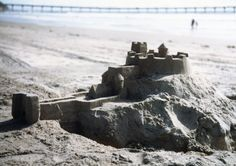 A sand castle with Ocean Beach Pier in the background.