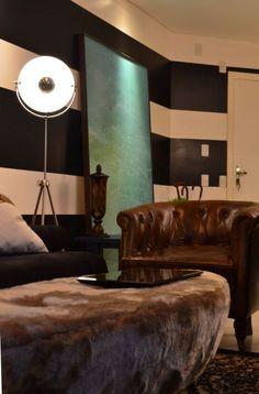 HELENAROCHAarquitetura - Sala de estar com puf oval e pelo cinza sintético e poltrona em couro marrom. Parede com listras pintadas e luminária estilo cine apoiada no chão.
