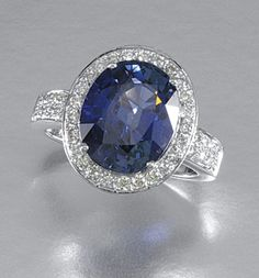 COLOUR-CHANGE SAPPHIRE AND DIAMOND RING Claw-set to the centre with an oval colour-change sapphire weighing 9.07 carats, within a border of brilliant-cut diamonds, to shoulders set with similarly cut stones