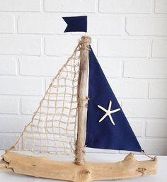 Our driftwood boats are made with real Driftwood found on the California Shores. This Driftwood Sailboat measures approximately 12-14 inches wide by 12-14 inches tall. We use Designer fabric on our sails. This Sailboat has navy blue fabric, Natural Netting and a real Starfish. You