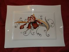 Plat décoré d'un iris rouge et noir et autour diverses techniques modernes : tressaillage, I relief, incrustation et blanc couvrant.