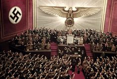 """Adolf Hitler receives a unanimous standing ovation from the entire German leadership upon concluding a fiery speech in which he officially declared that German troops have stormed into Poland. The final words of his address he proclaimed: """"If our will is so strong that no hardship and suffering can subdue it, then our will and our German might shall prevail!"""" The Reichstag, Berlin. September 2nd, 1939."""