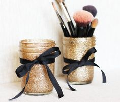 DIY glitter mason jars for makeup brushes, pens, or whatever you want to keep organized. Spray adhesive glue, swirl glitter, tie a bow... done! #DIY #Dorm #Storage