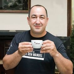 Rayco Rodriguez, owner of El Cafe de Don Manuel, which as won several awards for its coffee, holds up a cup of espresso.