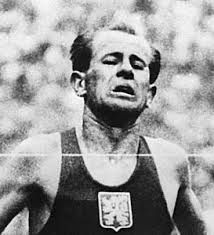 Emil Zatopek- The acme of the modern distance runner was Czech Zatopek, whose dominance and popularity was such that entire crowds would chant his name. His grimacing, head-rolling running style became famous, never more so than the 1952 Olympics in Helsinki, where he topped off the 5000 and 10,000m golds with his first marathon a couple of days later – and won. Zatopek was unbeaten at 10,000m between 1948-54 and broke 18 world records.