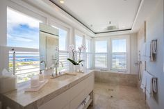 To make the most of the stunning views, the vanity and tilework sit below the windows. A frame-less glass shower also allows the eye to see straight through the bathroom to the beach beyond.