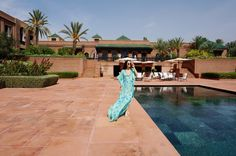 Anisa Sojka travels on holiday to Marrakech, Morocco and visits the luxurious Selman Hotel | Palm trees, sun beds, and a gigantic pool | She styles a Matthew Williamson mint green pineapple paisley print tiered maxi dress with black and gold classic Rayban round sunglasses