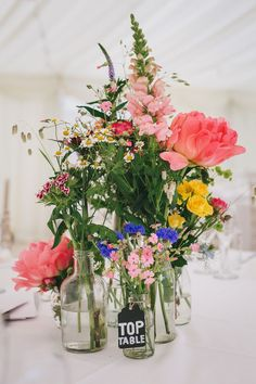 Bright Wild Flower Centrepieces - Helen Lisk Photography | Colourful Hanging Paper Lantern & Flower Filled Marquee Wedding | Bespoke Dresses & Tweed Suits