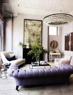 Antiqued mirror over fireplace, purple sofa, Chandelier