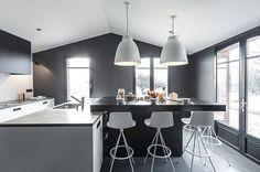 La cuisine blanche avec îlot central de cette longère rénovée a été relookée dans un style industriel. Plus de photos sur Côté Maison http://petitlien.fr/83en