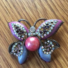 Vintage butterfly brooch Beautiful vintage brooch in pink and purple. Amazing detail with rhinestones and a large pink pearl bed in the center. Measures almost 2 inches in height. Vintage Jewelry Brooches
