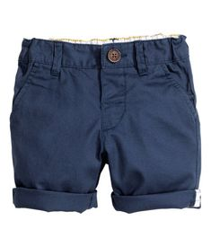 Shorts in woven cotton fabric. Adjustable elasticized waistband with button fly, side pockets, and mock welt pocket at back.
