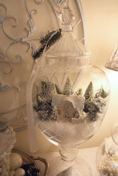 using an apothecary jar with plastic snow put a small cottage ornament on top and decorate it with trees and more snow