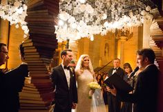 Clusters of light bulbs are inter-weaved with books to create an amazing archway at this library wedding.