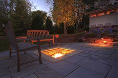 Fire pit terrace with teak benches at night.
