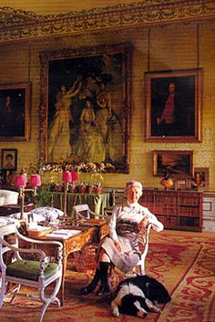Debo, Duchess of Devonshire, wearing a double strand of pearls with her knee socks below a John Singer Sargent painting in the Blue Drawing Room at Chatsworth in 1985. Photo by Derry Moore.