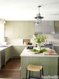 """Madeline Stuart concocted the """"modern Provincial"""" kitchen in a California house with minimalist grooved cabinetry, in a soft custom green, and limestone countertops. """"The kitchen needed to be somewhat masculine, but still warm and inviting,"""" she says."""