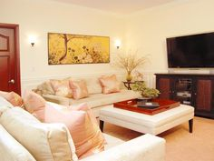 This stylish Asian themed living room features beautiful artwork, light toned furniture and entertainment area.
