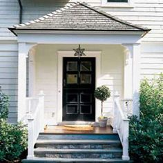 Entry porch with a flared hip roof and simple square columns with curved braces. Dutch door, bluestone steps, cedar porch columns with braces, finial-topped newel posts, and a pair of built-in benches round out the details. This Old House, House With Porch, House Front, Small Front Porches, Decks And Porches, Entry Doors, Entrance, Front Entry, Front Doors