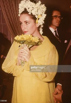 British-born actor Elizabeth Taylor, a yellow dress and floral headdress, holds a bouquet of flowers at her wedding to actor Richard Burton, March 15, 1964.