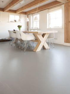 Gietvloer uit de Piet Boon Collectie van Ode aan de Vloer. De strakke, naadloze vloer laat vooral de robuuste eettafel en houten balken goed tot hun recht komen.