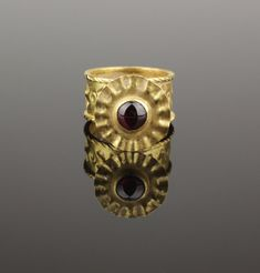 BEAUTIFUL ANCIENT BYZANTINE GOLD RINGANCIENT BYZANTINE GOLD & GARNET RINGTHIS BEAUTIFUL RING HAS A WIDE PIERCED DECORATED BANDWITH CROSS DECORATIONS,SUPPORTING A FLOWER TYPE BEZEL SET WITH A GARNET CABOCHONSOLID 22-24KT DATES: CIRCA 6TH/8TH CENTURY ADSIZE: US 7 & UK NWEIGHT : 9.1 GRAMS