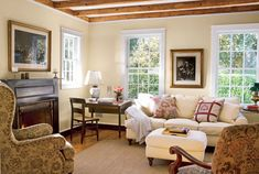 """The beauty of the floors and beams are 200 years' worth of nicks and crannies, warping, weathering, and nail holes. They look beautiful just as they are,"" says Richard.  In this photo: The buttercream-colored living room boasts original windows.   - CountryLiving.com"
