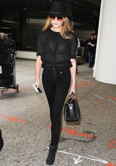 Street style Chrissy Teigen no aeroporto com look todo preto e chapéu.