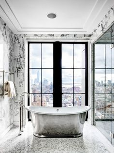 Penthouse bathroom with marble floors, a silver freestanding tub. and floor to ceiling window with a view of NYC's skyline