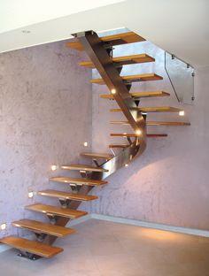 Escalier intérieur à limon central métallique, forme demi-tour. Cet escalier à limon central en inox est composé de marches en bois, sans contre marches avec garde-corps en verre le long de la deuxième volée. Un système d'éclairage à leds est intégré à l'escalier. Escalier métal design et moderne dans un intérieur chic et sobre de la gamme NEW-YORK by OéBa. Inspiration design staircase - Steel staircase.