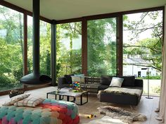 Love the pouffe !! (They call it an ottoman) Riverside house in Wales by Featherstone Young architects. Homes - Welsh House: Living room with floor to ceiling windows